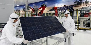 Two Qatar Solar Energy technicians handle a solar panel